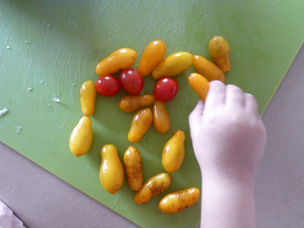 ילדה משחקת עם עגבניות שרי | צילום: שרון גולן